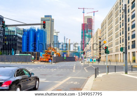 Frankfurt urban cityscape with car on crossroad, industrial plant building, cranes by skyscraper construction site in background, Germany