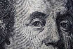 Franklin eyes macro. The texture of the fragment of the dollar bill. USD banknote texture. One hundred American dollars. Can  inform about fiscal and monetary policy of the country, currency inflati