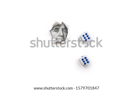 Franklin portrait in a torn hole of white paper and two dice 6. The concept of gambling, casino, losing and luck. Win or lose. Copy space.