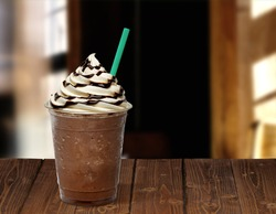 Frappuccino in plastic takeaway or to go cup on wooden table at cafe