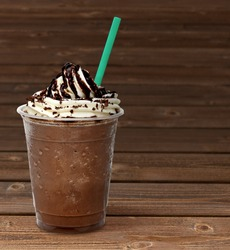 Frappuccino in takeaway cup on wooden table