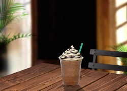 Frappuccino in takeaway or disposable cup on wooden table at cafe