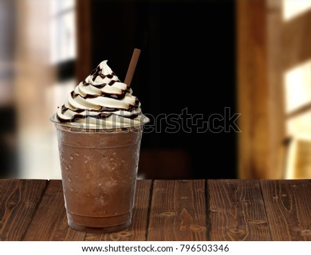 Frappuccino in takeaway or to go cup on wooden table at cafe #796503346