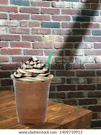 Frappuccino with cream and chocolate sauce in takeaway cup on wooden table #1409710913