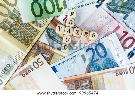 Fraud and Taxes written with cubes / letters and different euro bills as a background