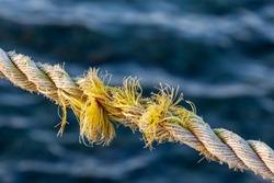 Frayed rope near to break on blue sea water background. Selective focus.