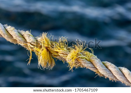 Frayed rope near to break on blue sea water background. Selective focus. Foto d'archivio ©