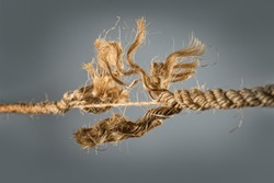 Frayed rope near to break on gray background. Selective focus