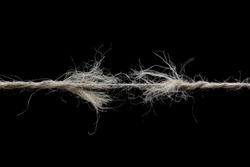 Frayed rope ready to break isolated on black background