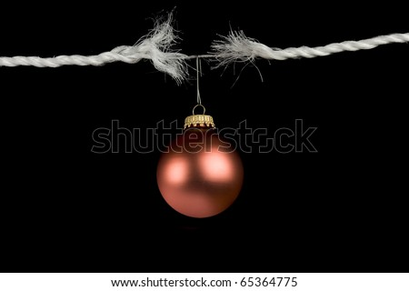 Frayed rope with christmas bulb holiday stress concept isolated on black background