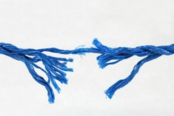 Fraying blue rope on white background showing concept of breaking strain, stress, tension, under pressure. With space for text