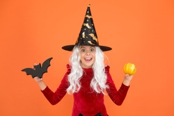Freakishly wicked Halloween. Little wicked witch child hold bat and pumpkin. Happy girl wear wicked witch costume. Small wicked sorceress with fashionable and frightful look.