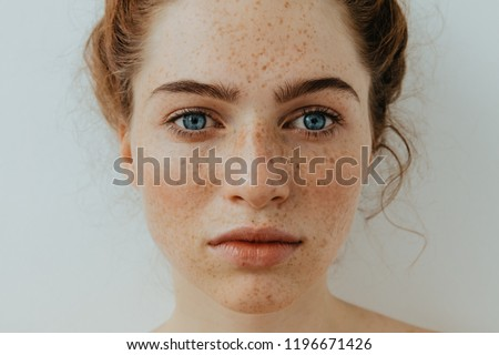Freckles Woman portrait. Close-up. Beautiful blue eyed girl with freckles is looking at camera, on a white background ストックフォト ©