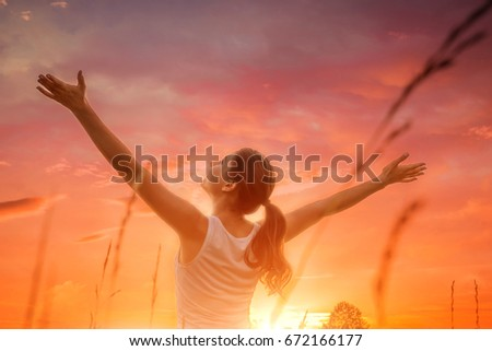 Free and happy woman raises arms against the sunset sky