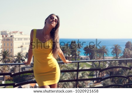 Free carefree happy girl in sexy dress standing in balcony and looking at sea. Nice, France (soft focus) #1020921658
