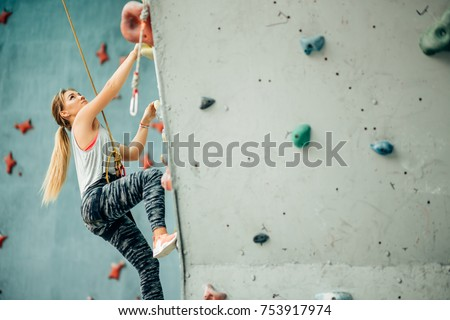 Free climber young woman climbing artificial boulder indoors #753917974