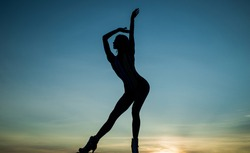 Free dance of woman ballet dancer silhouetted in dusk on evening sky, freedom