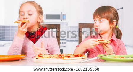Photo of Free delivery of pizza concept. Portrait of cute little child girls holding pizza slices as symbol of best food. Horizontal image.