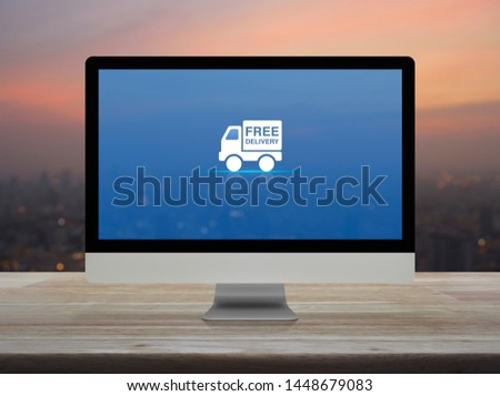 Free delivery truck flat icon on desktop modern computer monitor screen on wooden table over blur of cityscape on warm light sundown, Business transportation online concept #1448679083