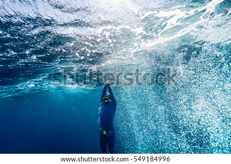 Free diver ascending from the depth in a rough sea with lots of bubbles.