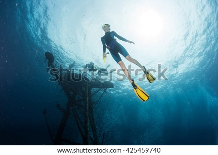 Free diver on depth with ship wreck on the background #425459740
