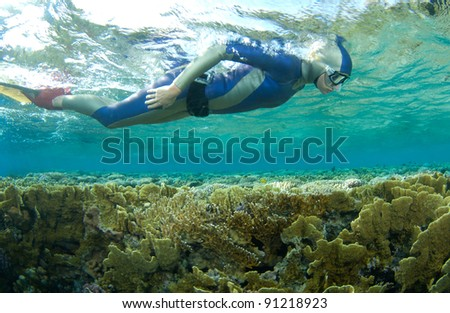 free diver with mono fin swim close to the coral reef