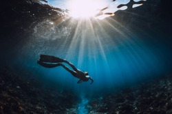 Free diver woman with fins glides over coral bottom and amazing sun rays. Freediving underwater in ocean