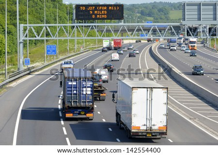 Free flowing traffic on  rural section of four lane dual carriageway M25 motorway in Essex England with active electronic overhead information sign
