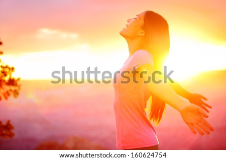 Photo of Free happy woman enjoying nature sunset. Freedom, happiness and enjoyment concept of beautiful multiracial Asian Caucasian girl in her 20s. Image from Grand Canyon, United States.