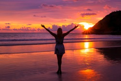 Free happy woman raising arms watching the sun in the background at purple sunset.