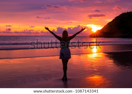 Free happy woman raising arms watching the sun in the background at purple sunset. #1087143341