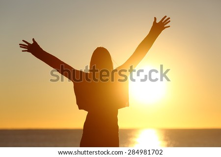 Free happy woman raising arms watching the sun in the background at sunrise