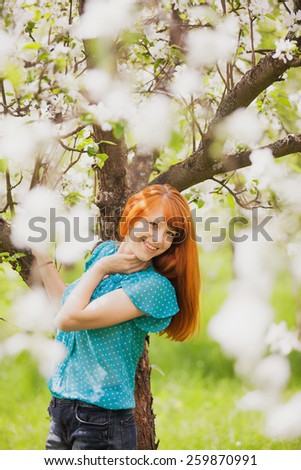 Free Happy Woman with Gorgeaos Red Hair Enjoying Nature. Beauty Young Girl Outdoor in Spring Garden. Freedom concept. Healthy Smiling Girl over Green Flowers Nature Background. Apple-trees in Blossom