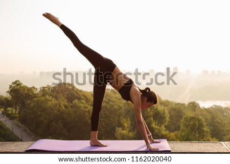 Free leg dog. Full length of young beautiful fit woman in sportswear doing yoga against industrial city view #1162020040