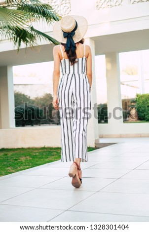 Free like a bird. A bodacious women facing the virid palm tree wearing a taupe hat with a coal coloured bow on the back part of it, great fitting jumpsuit and leather peeps. #1328301404