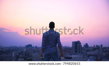 Free man standing on roof edge at dusk, desire to find strength and independence