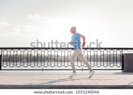 Free of movements. Aged athletic unshaken man being on the quay doing cardio exercises and running. #1051240046