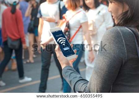 free public Wifi concept.Young woman holding mobile phone on blurred people walking as background Foto stock ©