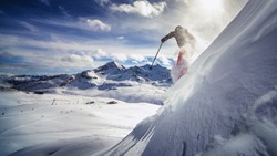 Free ride skier, skiing down steep slope, good background with blue skies and mountains
