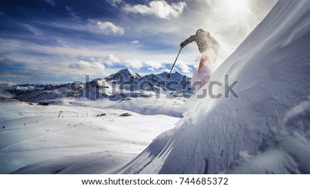 Free ride skier, skiing down steep slope, good background with blue skies and mountains  #744685372