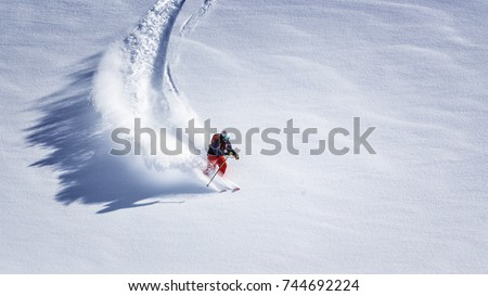 Free ride skier skiing down through fresh powder