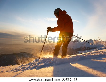 Free-rider skier moving down in snow powder at sunset; italian alps.