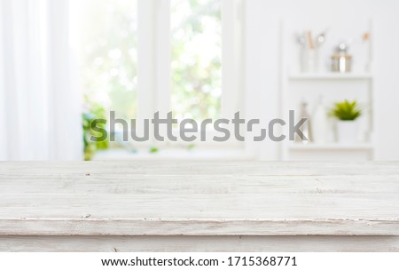 Photo of  Free space table top background on blurred kitchen window interior