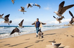 Free spirited young man running on the beach with the birds flying.