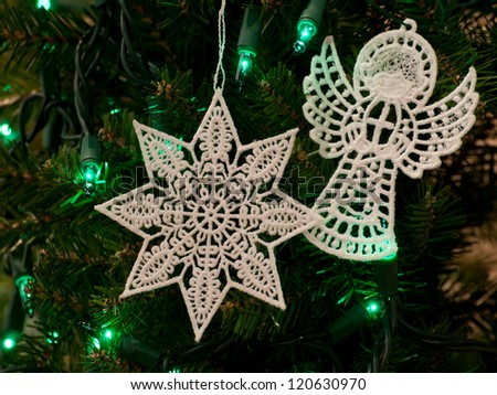Free-standing lace Christmas star and Christmas angel ornaments on tree with green lights