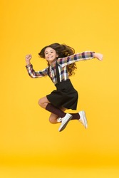 Free style. Happy schoolchild in midair yellow background. Free from school. Summer holidays. Free time. All good things are wild and free.