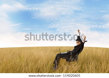 Free successful businessman with laptop in the field