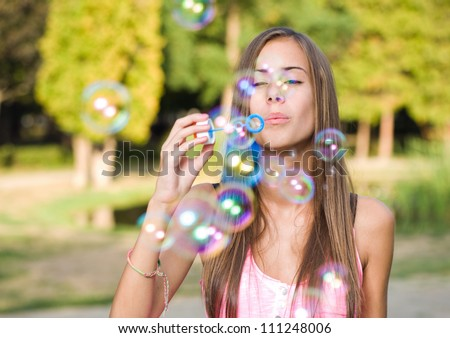 Free the bubbles, portrait of a beautiful young girl having fun outdoors blowing soap bubbles.