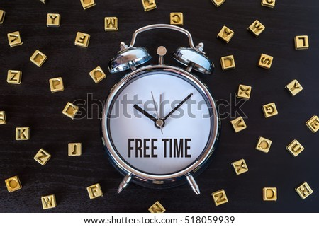 Free time - Alarm clock on wooden table with letters