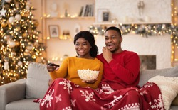 Free time, favorite movie and self-isolation at home. Millennial funny african american husband and wife with remote control and popcorn covered with blanket and watching tv in interior with tree